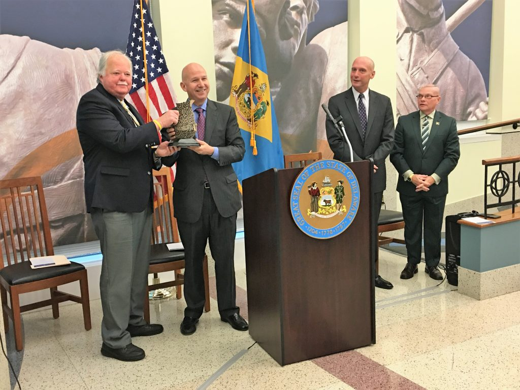 Edward J. Freel accepts the 2016 Governor's Heritage Award from Governor Jack Markell as Secretary of State Jeffrey Bullock and State Archivist Stephen M. Marz look on