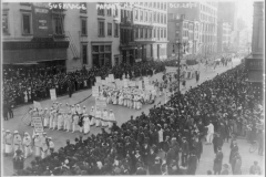 Forty thousand march in a NYC suffrage parade. Many women are dressed in white and carry placards with the names of the states they represent