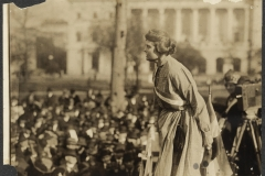"""Suffragist Lucy Branham in an Occoquan Prison dress in 1919. Branham was speaking at an outdoor meeting during the National Woman's Party """"Prison Special"""" tour. She is above a large crowd, wearing a prison dress and suffrage sash, with a suffrage flag and camera on a tripod right behind her."""