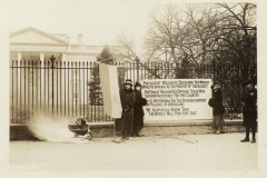 The National Women's Party watches as a fire burns outside of the White House in January 1919.